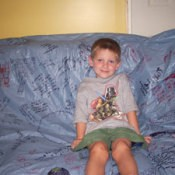 Child sitting on couch covered with keepsake tablecloth.