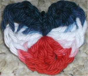 Crochet red, white, and blue heart shaped pin.
