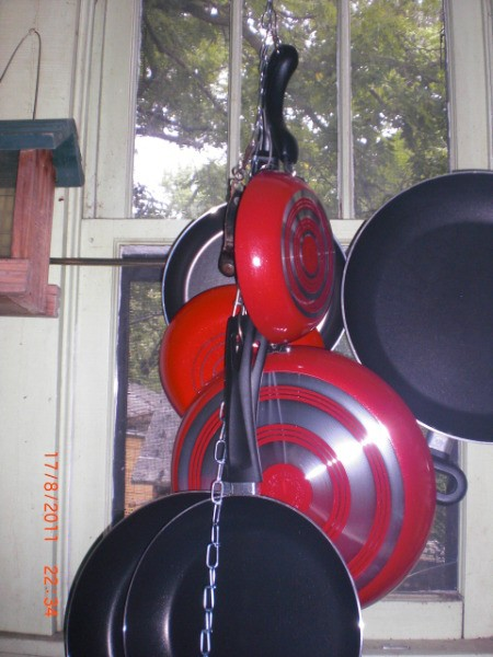 Pots hanging from a chain in the kitchen.