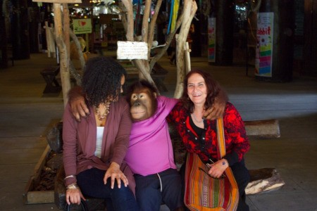 Two women on a bench with the orangutan.