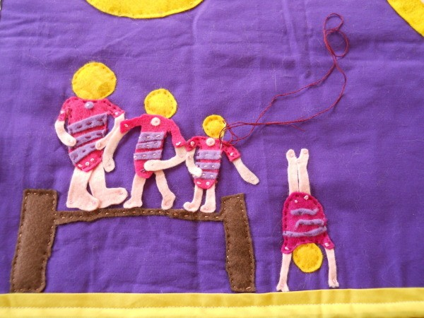 Close up of gymnasts while sewing onto rug.