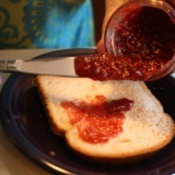 Homemade raspberry jam being spread on a piece of bread