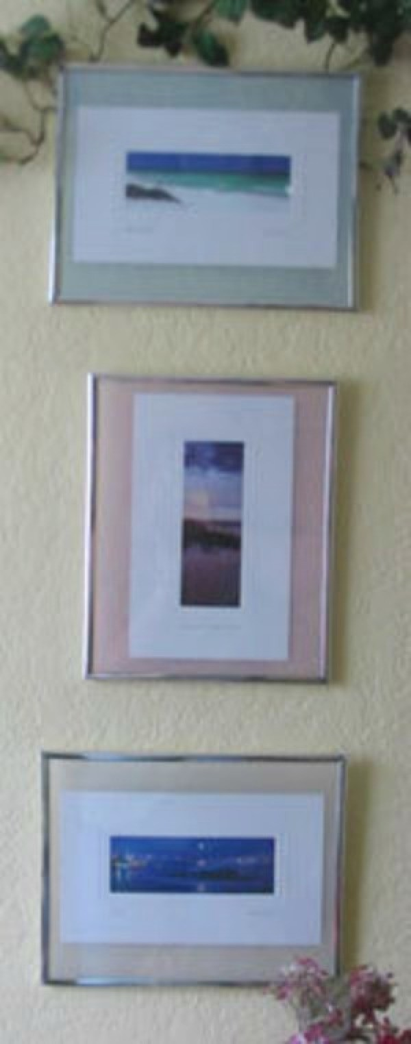 Three frames containing postcards mounted on a wall.