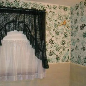 White wall with dark green sponge painting.