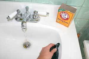 Cleaning sink with baking soda.