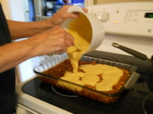 Pouring cornbread batter onto meat mixture.
