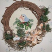 Wreath with cross stitch mounted in center.