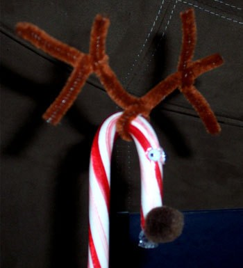 Candy cane decorated with pipe cleaner, google eyes, and a pom pom.