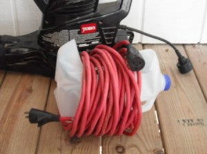 Leaf blower cord wrapped around a modified milk jug.