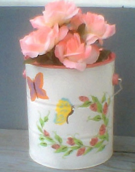 White paint can with spray of pink flowers and butterflies.