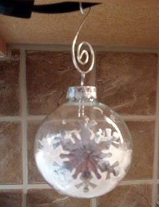 Snow filled glass ornaments with snowflake stickers.