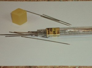 Pencil lead tube with a variety of sewing needles.