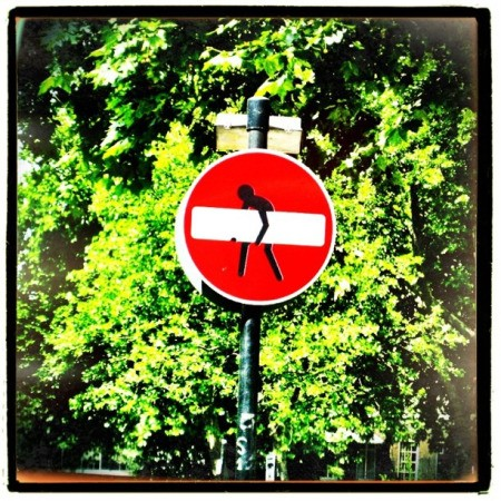 Man carrying away white line on red sign.