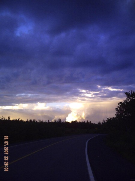 Bright light on the horizon with dark clouds above.
