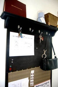 Black message board with shelf above.