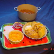 Tray of food on blue background with Dutch oven in background of frame.