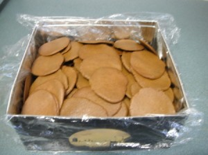 Baked cookies in a box covered with Saran Wrap.
