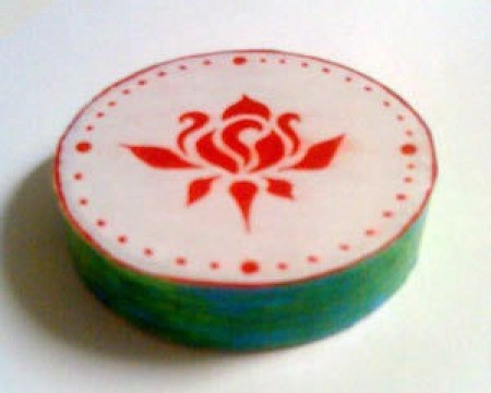 """Finger drum made from a roll of tape with decorative designs on the """"drumskin""""."""