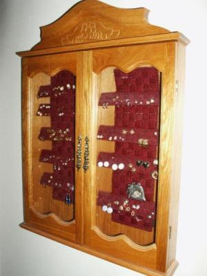 Box mounted on wall, filled with earrings, and doors closed.