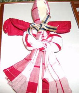 Red and white dish towel folded to resemble an angel.