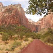 Red road leading towards red rock sandstone formations.