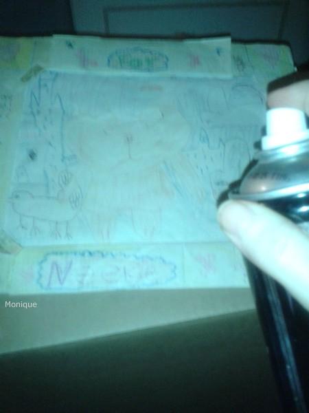 Spraying hairspray on a drawing.