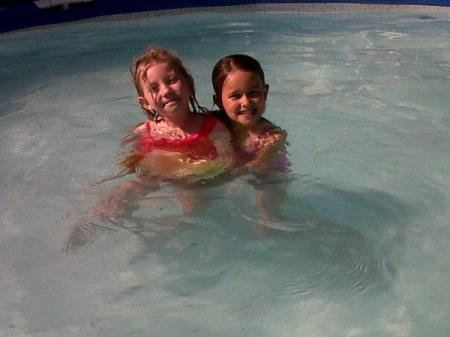 Two young children in a pool.