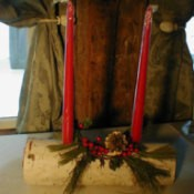 Birch log with two red candles in drilled holes.