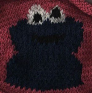 A knitted sweater with the Sesame Street character Cookie Monster.