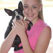 Smiling teenage girl holding her black and white small dog