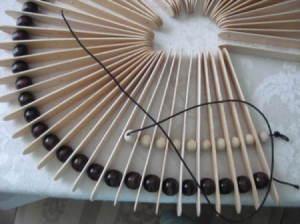 Closeup of threading smaller beads.