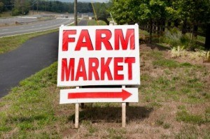 A sign pointing to a farmers market.
