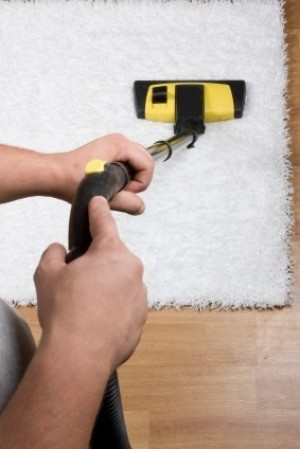 A person cleaning a rug.