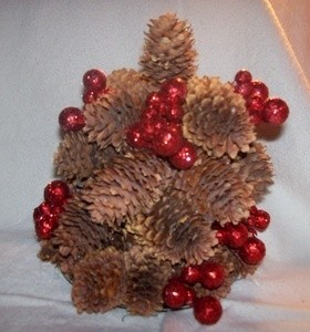 Pinecones glued to CD to resemble a tree and decorated with red berries.