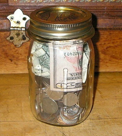 Money Jar full of coins and a $20 bill.
