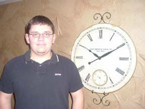 Teenage boy next to clock.