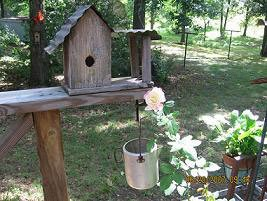 A wooden birdhouse near a rose.