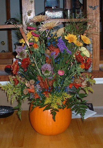 A fall floral display inside a pumpkin vase.