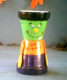 Two clay pots decorated to make a smiling Frankenstein monster candy dish.