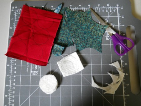 Sewing grid board with cut out leaves, circles of batting for berries and a pair of scissors.