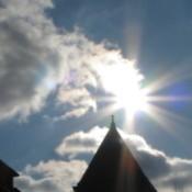 Sun shining over steeple.