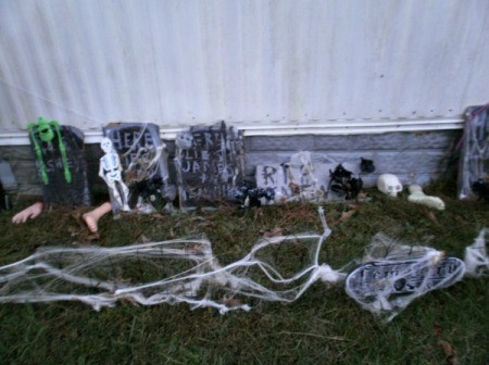 Tombstones outside of home decorated with spider webbing, skeletons, etc.