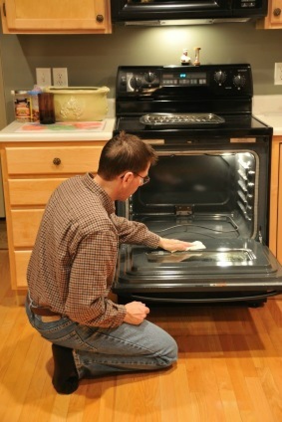 Man Cleaning Glass Oven Door