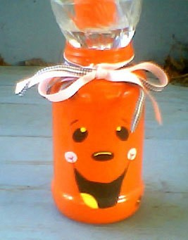 Halloween candle centerpiece made from jar painted like a jack-o-lantern.