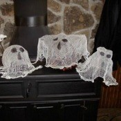 Ghosts made from cheesecloth sitting on woodstove.