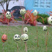 Painted gourds on sticks in yard.