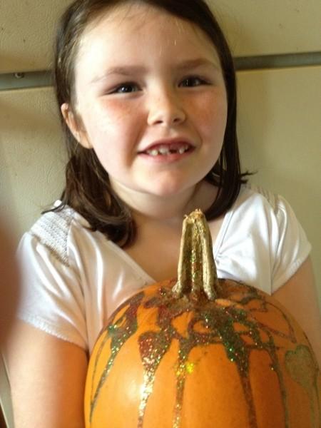 Little girl holding glitter decorated pumpkin.