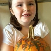Little girl holding glitter decorated pumpkin.