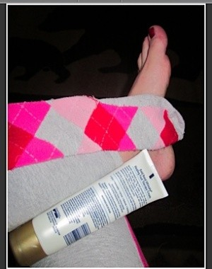 Tube of lotion, sock, and foot.