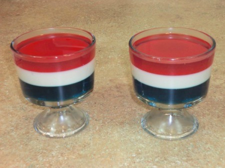 Two clear dishes of red, white, and blue Jello parfait.